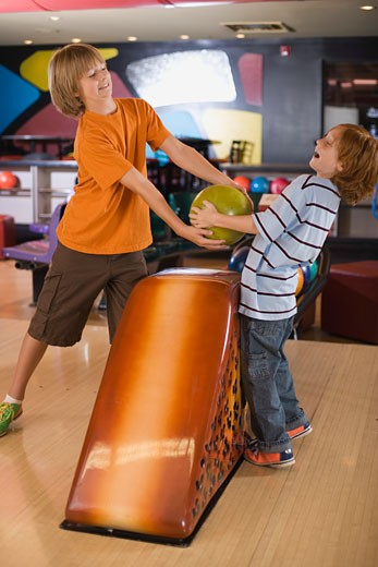 Stock Photo: 1555R-310259 Boys fighting over bowling ball
