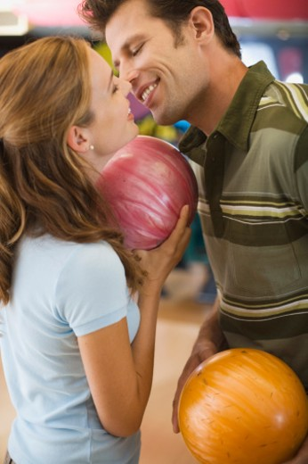 Couple with bowling balls about to kiss : Stock Photo