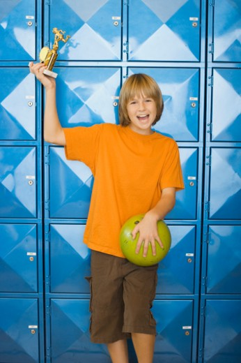 Boy holding trophy and bowling ball : Stock Photo