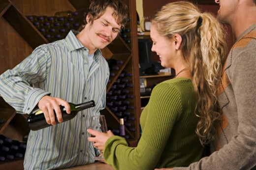 Man pouring wine for couple at wine tasting : Stock Photo