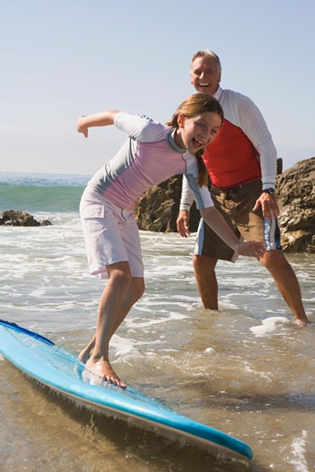 Man watching girl ride surfboard on shore : Stock Photo