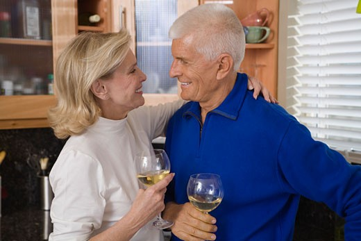 Affectionate senior couple with wine glasses : Stock Photo