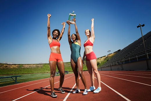 Athletic women holding up trophy : Stock Photo