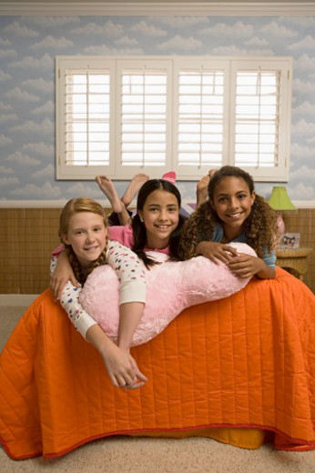 Stock Photo: 1555R-312148 Three preteen girls lying on bed