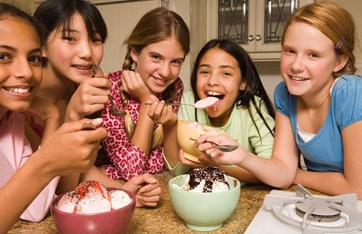 Group of preteen girls eating ice cream sundaes : Stock Photo