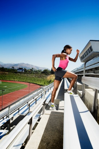 Stock Photo: 1555R-312235 Athletic woman running up bleachers