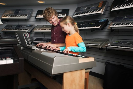 Man and girl playing keyboard together in music store : Stock Photo