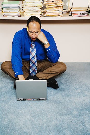 Man sitting on floor of office with laptop computer : Stock Photo