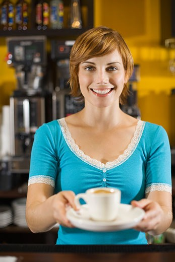 Stock Photo: 1555R-313772 Smiling woman serving coffee