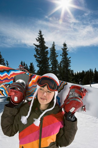 Stock Photo: 1555R-314045 Woman carrying snowboard