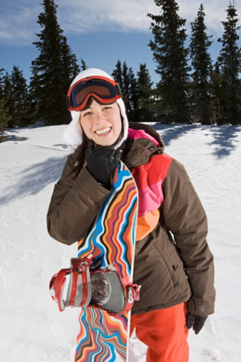 Smiling woman with snowboard : Stock Photo