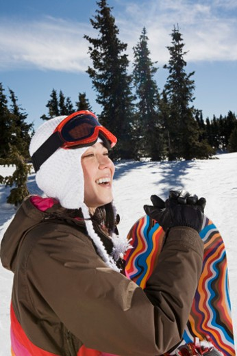 Stock Photo: 1555R-314050 Side view of woman with snowboard