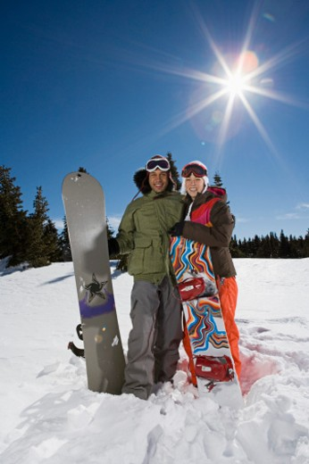 Couple posing with snowboards on sunny winter day : Stock Photo