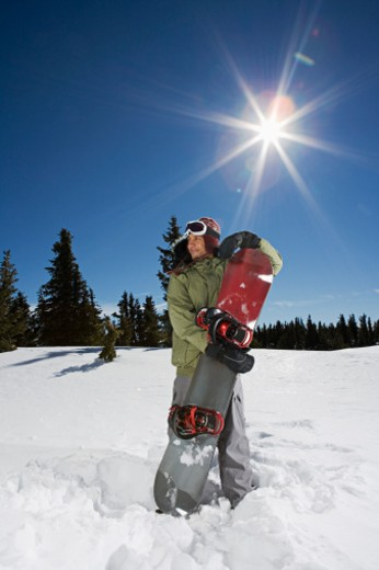 Man standing with snowboard : Stock Photo