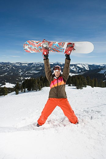Stock Photo: 1555R-314069 Woman lifting snowboard over head