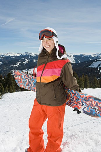 Stock Photo: 1555R-314076 Smiling woman holding snowboard