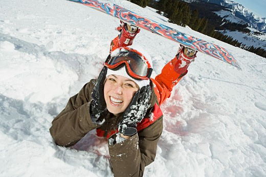 Woman with snowboard lying on snow : Stock Photo