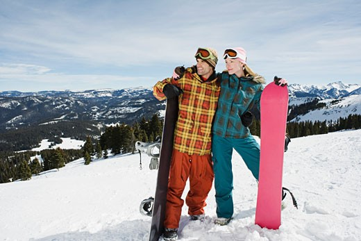 Snowboarding couple looking away : Stock Photo