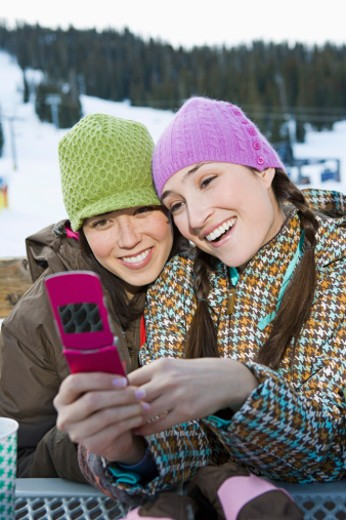 Friends looking at cell phone : Stock Photo