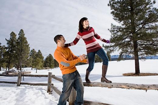 Stock Photo: 1555R-314106 Man helping woman walk along fence