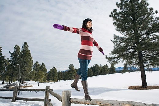 Woman balancing on top of fence : Stock Photo