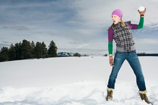 Stock Photo: 1555R-314131 Woman throwing snowball
