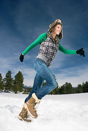 Woman running in snow : Stock Photo
