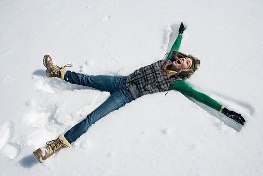 Woman making snow angel : Stock Photo
