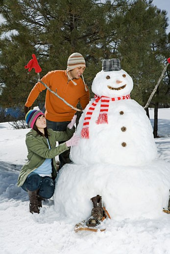 Couple making snowman : Stock Photo