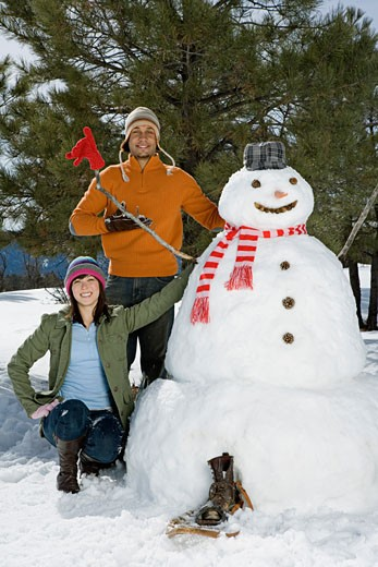 Stock Photo: 1555R-314157 Couple posing with snowman