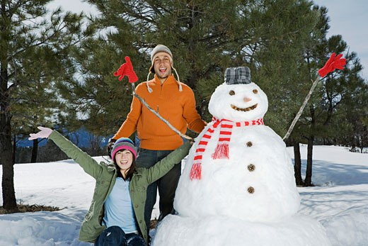 Stock Photo: 1555R-314158 Couple finished making snowman