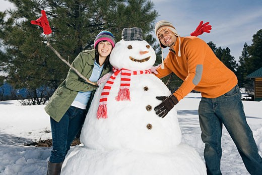 Stock Photo: 1555R-314160 Couple posing with snowman