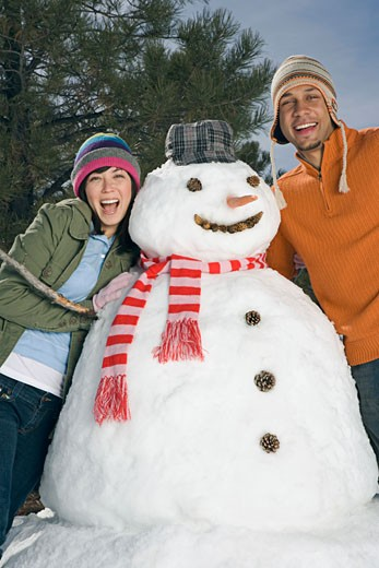 Stock Photo: 1555R-314161 Happy couple posing with snowman