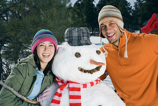 Stock Photo: 1555R-314163 Smiling couple posing with snowman