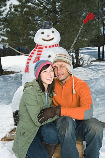 Stock Photo: 1555R-314165 Seated couple with snowman