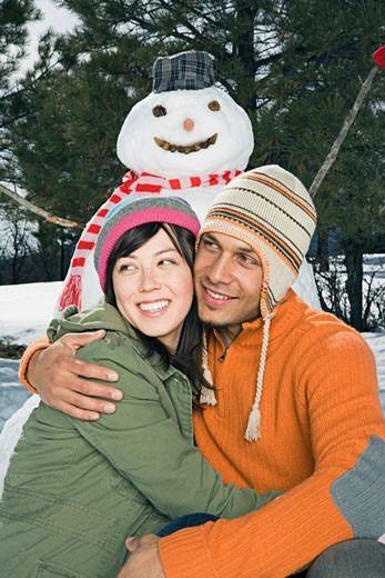 Stock Photo: 1555R-314167 Embracing couple with snowman