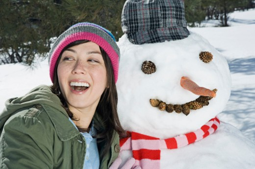 Stock Photo: 1555R-314171 Woman kissing snowman