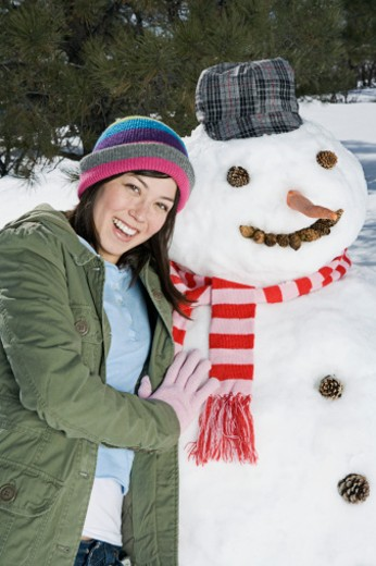 Woman posing with snowman : Stock Photo