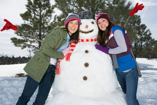 Women posing with snowman : Stock Photo