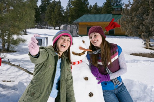 Women taking a picture with snowman : Stock Photo