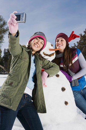 Stock Photo: 1555R-314177 Women taking a picture with snowman