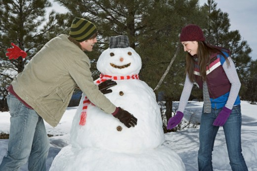 Couple making snowman together : Stock Photo