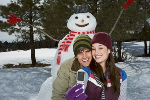 Couple taking a picture with snowman : Stock Photo