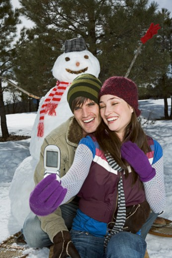 Stock Photo: 1555R-314184 Couple taking a picture with snowman