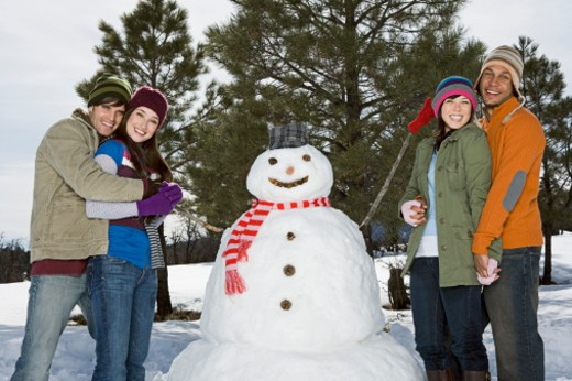 Couples together with snowman : Stock Photo