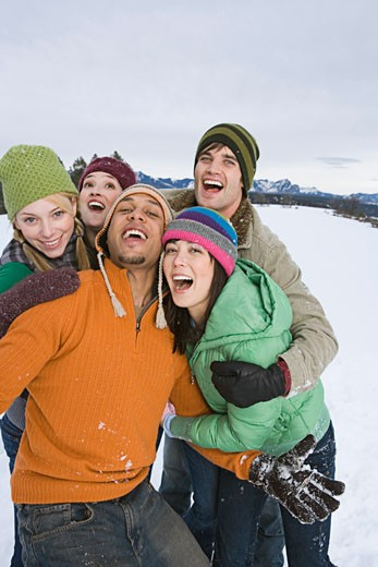 Friends having fun in snow together : Stock Photo