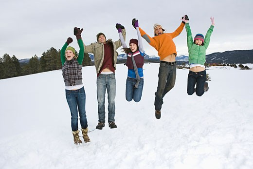 Friends jumping in snow : Stock Photo