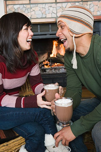 Laughing couple having hot cocoa by fireplace : Stock Photo