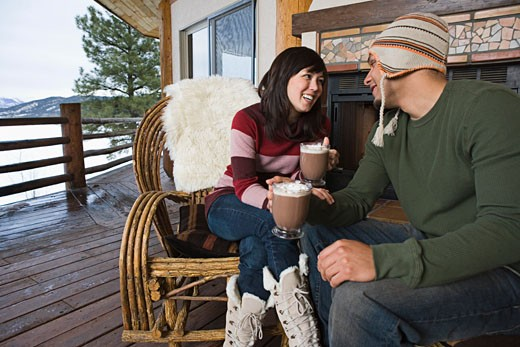 Couple drinking hot cocoa on deck : Stock Photo