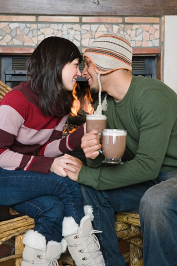 Stock Photo: 1555R-314211 Couple face to face by fireplace